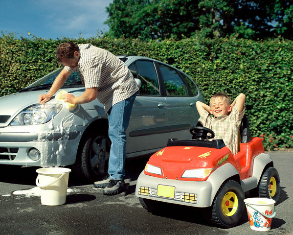 Father Cleaning His Car and Son Relaxing in Toy Car --- Image by © Gary Salter/Corbis